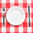 Knife, white plate and fork on red checked tablecloth — Stock Photo