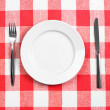 Royalty-Free Stock Photo: Knife, white plate and fork on red checked tablecloth