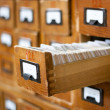Old wooden card catalogue with one opened drawer - Foto Stock