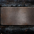 Metal plate over burned wooden background — Stock Photo