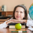 Schoolgirl's portrait at school desk with her books and globe — Stock Photo