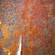 Stock Photo: Torn rusty metal texture with rivets over red background