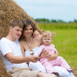 Stock Photo: Happy family in haystack or hayrick