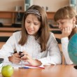 Stock Photo: Two girls are using mobile phone with interest