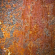 Torn rusty metal texture with rivets over red background — Stock Photo