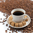 Coffee cup on heap of coffee beans — Stock Photo