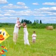 Stock Photo: Happy family with pregnant wife fly a kite together in summer fi