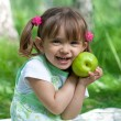 Little girl portrait with green apple in her hands outdoor — Stock Photo #5313336