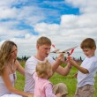 Happy family launching toy aircraft model together — Stock Photo
