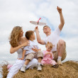 Royalty-Free Stock Photo: Happy family launching toy aircraft model sitting on haystack to