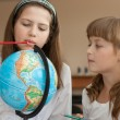Two schoolgirls search geographical location using globe — Stock Photo