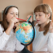 Stock Photo: Two schoolgirls search geographical location using globe