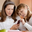 Stock Photo: Two girls sitting at school desk with mobile phone