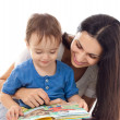 Stock Photo: Mother and son reading book together isolated on white