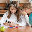 Two girls sitting at school desk with mobile phone — Stock Photo