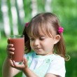 Little girl portrait with glass plum or cherry juice outdoor — Stock Photo