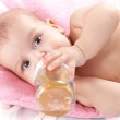 3 months adorable baby girl drinking from plastic bottle in her — Stock Photo #5315340
