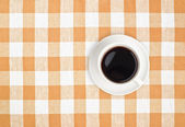 Top view of black coffee cup on brown checked tablecloth — Stock Photo