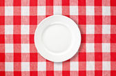 Orange plate on red checked tablecloth — Stock Photo