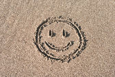 Smiley face drawn on bach sand — Stock Photo