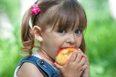 Little girl portrait eating red apple outdoor — Stock Photo