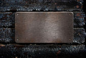 Metal plate over burned wooden background — Fotografia Stock