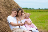 Happy family in haystack or hayrick — Stock Photo