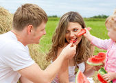 Happy family in haystack feeding mother with watermelon — Stock Photo