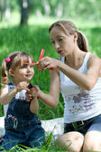 Mother and daughter in jeans with toy outdoor — Stock Photo