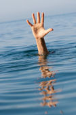 Single hand of drowning man in sea asking for help — Stock Photo