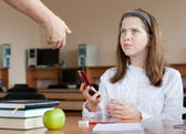 Teacher confiscates mobile phone at lesson — Stock Photo