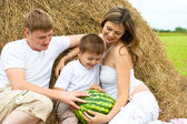 Happy family in haystack or hayrick with watermelon — Stock Photo
