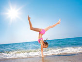 Schoolgirl making gymnastics on seashore — Stock Photo