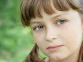 Fullface portrait of serious little girl with beautiful green ey — Stock Photo