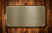 Brass metal plate on wooden background — Stock Photo