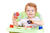 Baby girl with blue eyes creates picture sitting at table with p — Stock Photo