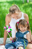 Smiling mother and daughter in jeans with colorful toy outdoor — Stock Photo