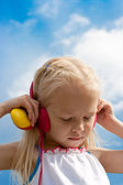 Little blonde girl with closed eyes red earphones listen mp3 pla — Stock Photo
