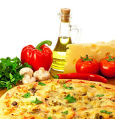 Pizza and ingredients with focus on pizza — Stock Photo