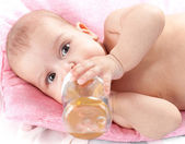 3 months adorable baby girl drinking from plastic bottle in her — Stock Photo