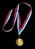Golden medal isolated on black — Stock Photo
