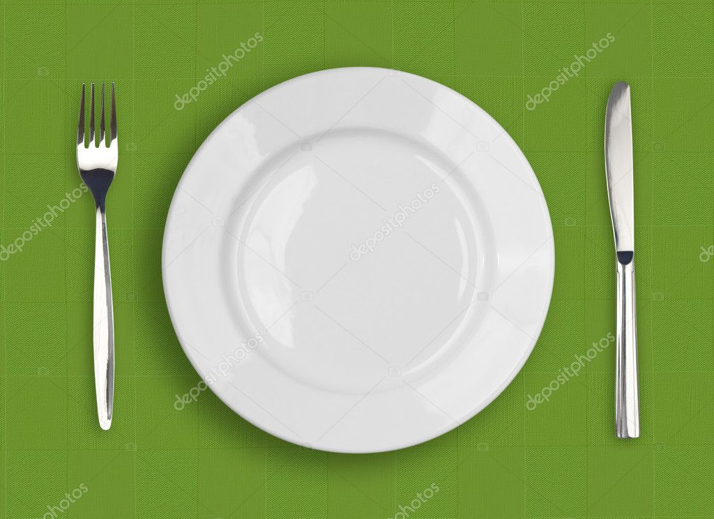 Knife, white plate and fork on green background — Stock Photo #5312324