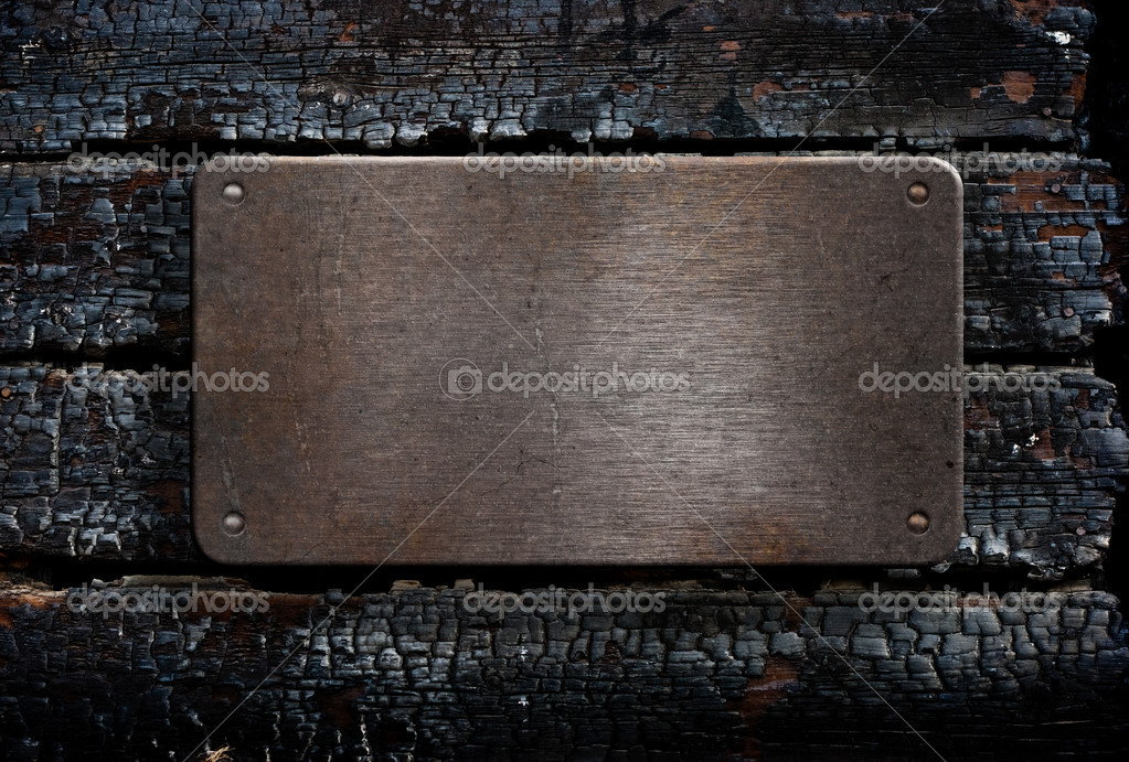 Metal plate over burned wooden background — Stock Photo #5313138