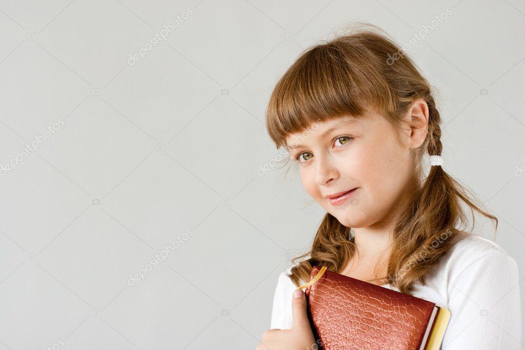 Cute preteen schoolgirl portrait near whiteboard - Stock Image