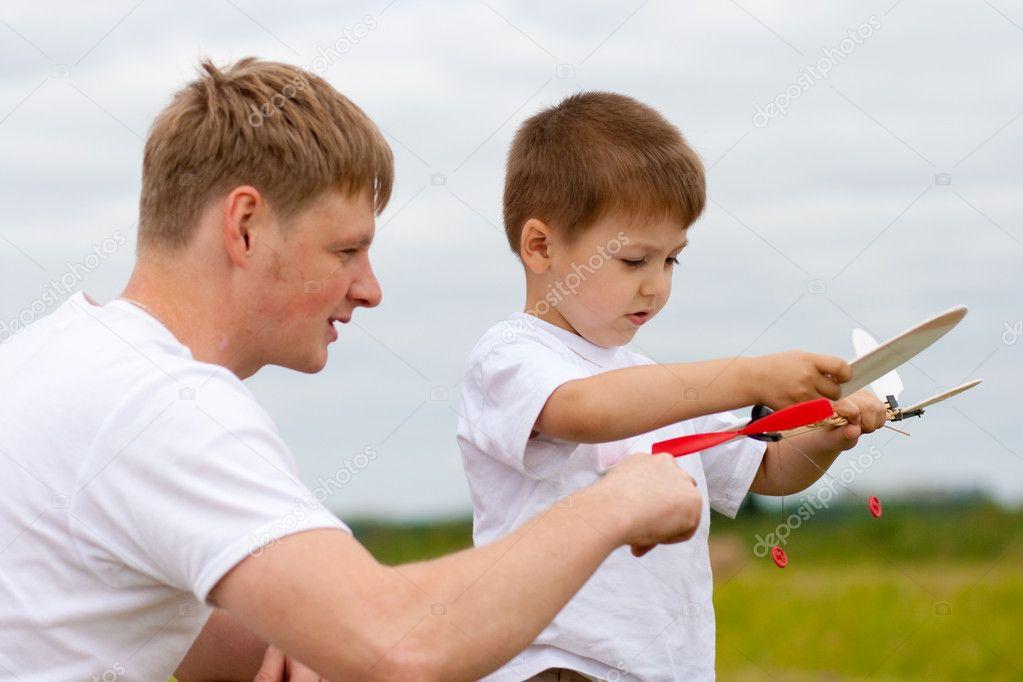 父亲和儿子玩玩具飞机模型在公园