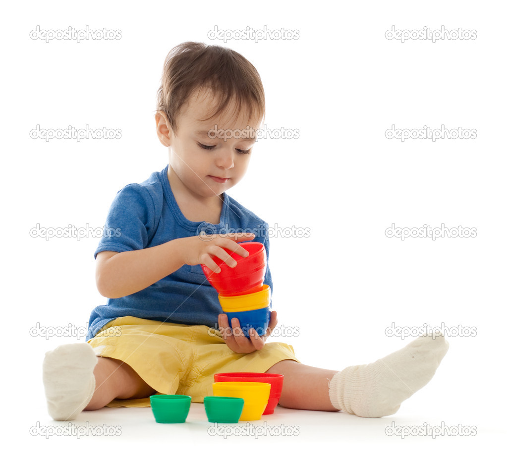 Cute little boy is playing with colorful cups isolated on white  Stock Photo #5314311