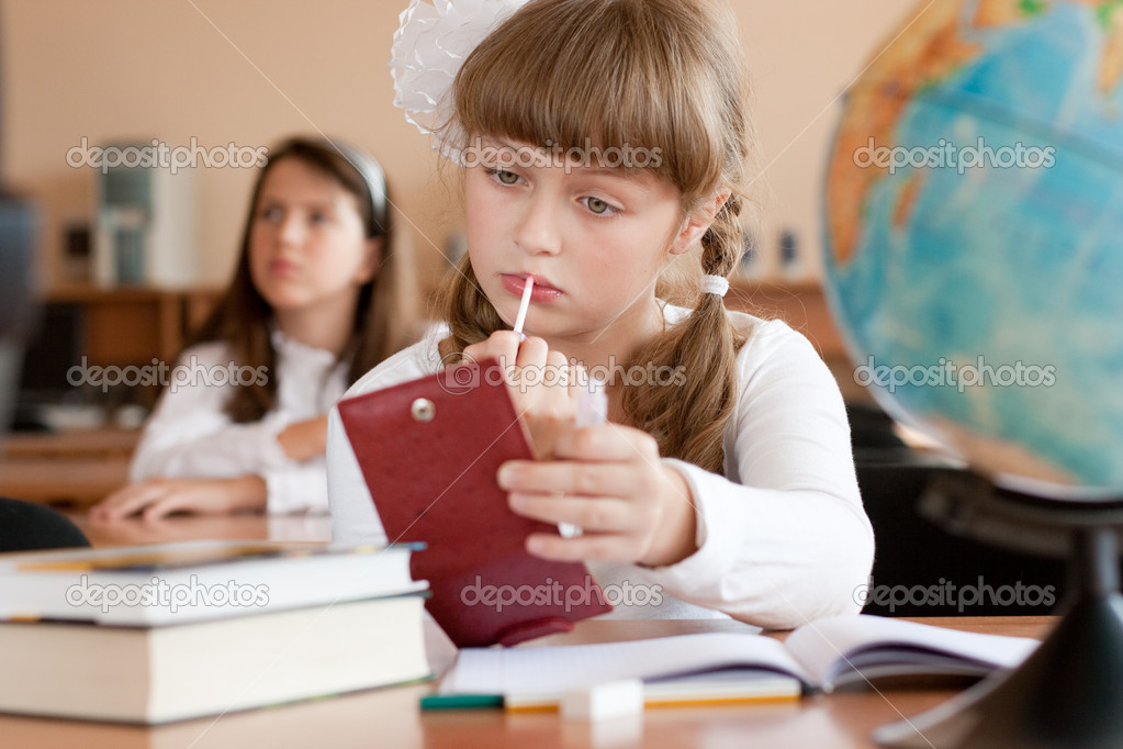 Cute preteen schoolgirl is making make-up during lesson at schoo ...