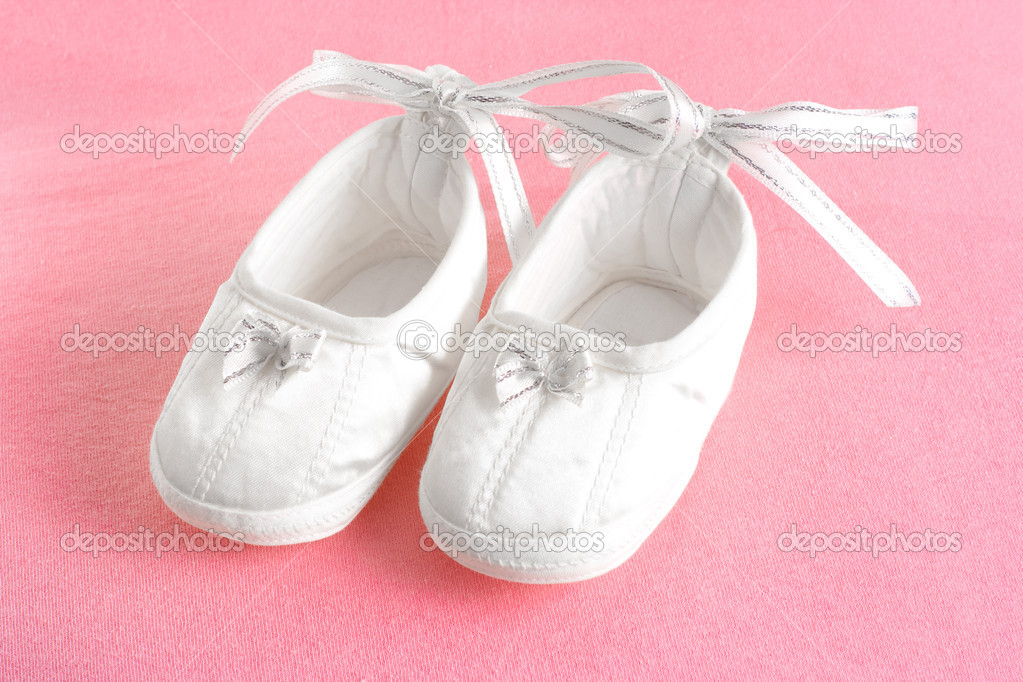 White baby's bootees on pink sheet  Stock Photo #5315532