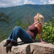Woman Sitting On A Rock - Stock Photo