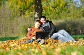 Happy family with notebook under tree in autumn — Stock Photo